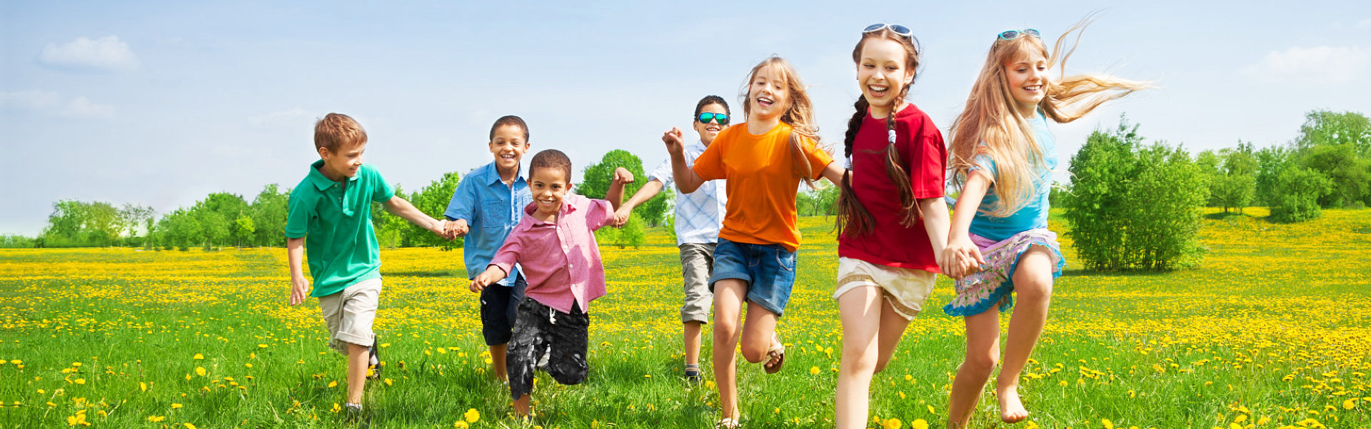 group of kids running in the dandelion spring field